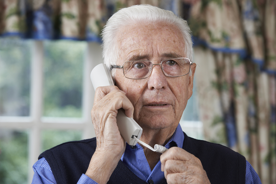 Worried older man answers a telephone.